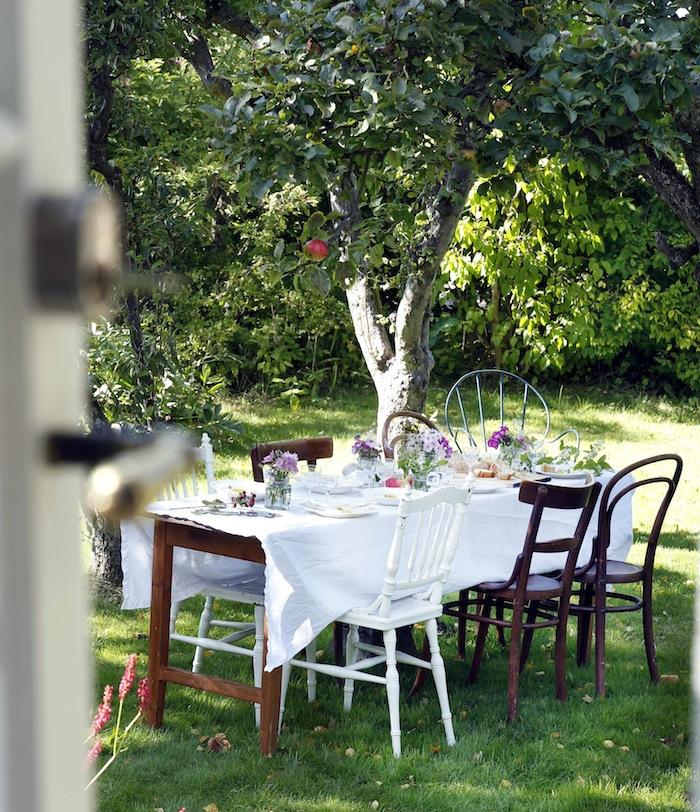 Home stories dukning under äppelträd, blandade stolar, blommor